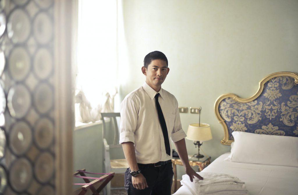 ethnic male maid arranging hotel room