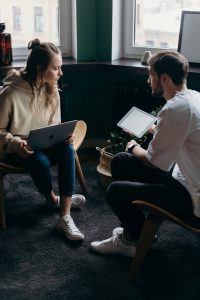 photo of couple talking while holding laptop and ipad
